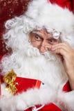 在红色隔绝的圣诞老人饮用的茶特写镜头画象 免版税库存照片