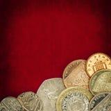 在红色难看的东西背景的英国硬币 库存图片