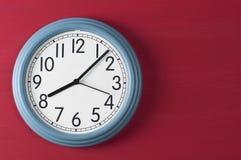 在红色难看的东西背景的蓝色壁钟 免版税库存图片