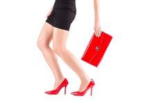 在红色鞋子和袋子的女性腿在手中 免版税图库摄影