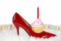 在红色鞋子的生日杯形蛋糕在毛皮 免版税库存照片