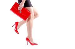 在红色鞋子的美好的走的女性腿 免版税库存图片