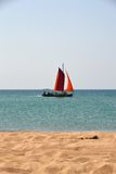 在红色风帆下的小船在海 库存照片