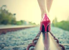 在红色高跟鞋的女性腿在铁路的路轨 免版税库存照片