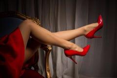在红色高跟鞋的女性腿 免版税库存图片