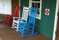 在红色,白色和蓝色颜色的3把室外木摇椅 免版税库存照片