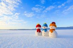 在红色,蓝色,黄色帽子和围巾的朋友雪人 与山的好的冬天风景,在雪的领域 橙色日落背景 免版税库存图片