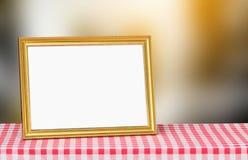 在红色织品桌面的金黄画框与拷贝空间和 库存图片