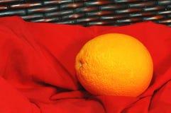 在红色织品的橙色果子 库存图片