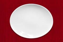 在红色织品的白色卵形板材 免版税库存照片