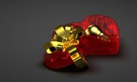 在红色玻璃心形的箱子的金黄电灯泡 免版税库存图片