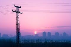 在红色紫色多云日落的电源杆剪影 免版税库存图片