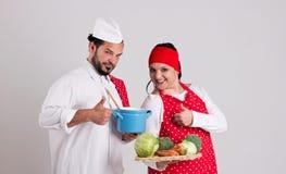 在红色围裙的意大利语Chiefcook和英俊的Cooky显示Nu 免版税库存照片