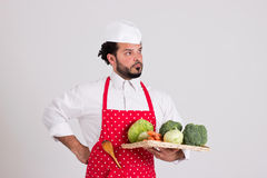 在红色围裙的意大利语Chiefcook拿着有Veget的柳条盘子 免版税库存图片