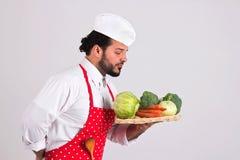 在红色围裙的意大利语Chiefcook拿着有Veget的柳条盘子 免版税图库摄影