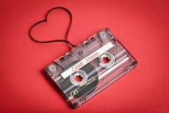 在红色backgound的卡型盒式录音机磁带 塑造心脏的影片 免版税库存图片