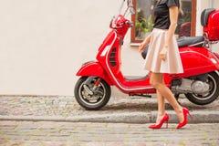 在红色moto滑行车前面的夫人 免版税图库摄影