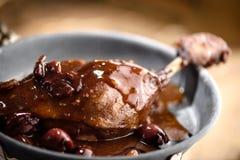 在红葡萄酒樱桃调味汁的烤鸭子腿 图库摄影