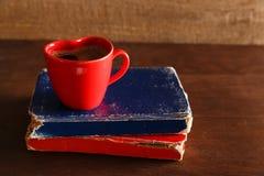 在红颜色心脏形状杯子的咖啡有旧书的 免版税库存图片