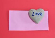 在红颜色泡沫的桃红色信封和心脏石头上 免版税库存照片