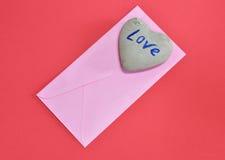在红颜色泡沫的桃红色信封和心脏石头上 免版税库存图片