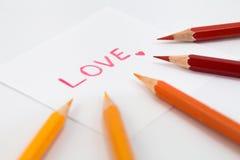 在红颜色的字词爱与在小纸的一点心脏,包围与在温暖的口气的颜色铅笔 图库摄影