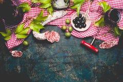 在红细胞棉花桌布的意大利开胃菜快餐用蒜味咸腊肠、橄榄和红葡萄酒,黑暗的土气背景 库存照片
