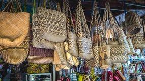 在纪念品店前面的藤条提包在沙马林达,印度尼西亚 库存图片