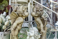 在纪念品店窗口里以为特色的天使小雕象 库存图片