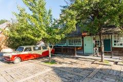 在纪念品店附近的汽车在Drvengrad,塞尔维亚 库存图片