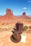 在纪念碑谷前面的启动和帽子 库存图片