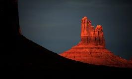 在纪念碑谷小山的光芒四射的红色日落焕发 库存图片