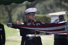 在纪念仪式的海洋折叠的旗子下落的美国战士的, PFC扎克苏亚雷斯,在高速公路23,对纪念Ser的驱动的荣誉使命 库存图片