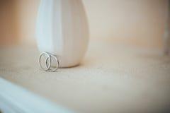 在纯净的白色桌上的婚戒 库存图片