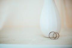 在纯净的白色桌上的婚戒 库存照片