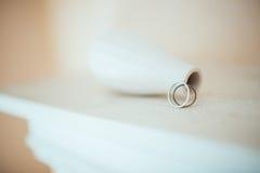 在纯净的白色桌上的婚戒 图库摄影