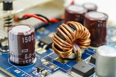 在纯铁圆环的变压器在电路板特写镜头 免版税库存照片