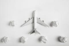 在纸云彩中的飞机式样飞行 图库摄影