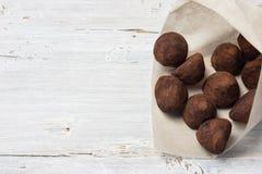 在纸包装的块菌状巧克力糖果在白色后面 免版税库存照片
