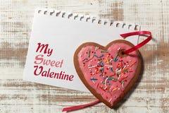 在纸和曲奇饼心脏的情书与在木土气书桌上的红色丝带 库存照片