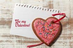 在纸和曲奇饼心脏的情书与在木土气书桌上的红色丝带 图库摄影