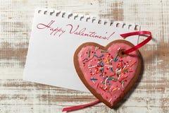 在纸和曲奇饼心脏的情书与在木土气书桌上的红色丝带 免版税库存图片
