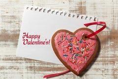 在纸和曲奇饼心脏的情书与在木土气书桌上的红色丝带 免版税库存照片