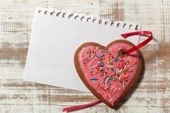 在纸和曲奇饼心脏的情书模板与在木土气书桌上的红色丝带 免版税库存照片