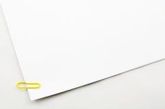 在纸张的黄色回形针 免版税库存图片