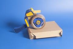 在纸板箱的工业磁带分配器 免版税库存照片