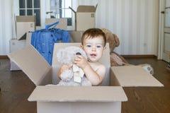 在纸板箱藏品和包装里面的逗人喜爱的矮小的男婴他的玩具玩具熊在有大箱子的屋子里在背景 免版税库存照片