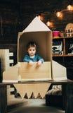 在纸火箭的小男孩戏剧,童年 地球日概念 教育和孩子想法发展 旅行和冒险 免版税库存照片