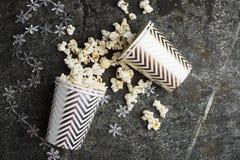 在纸灰色白色圣诞节杯子的玉米花与朋友的寒假会谈的有新年` s圣诞节装饰的 免版税库存图片