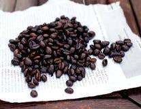 在纸片的咖啡豆 木背景 免版税库存照片